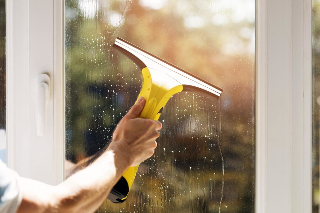 professional exterior cleaner cleaning residential windows