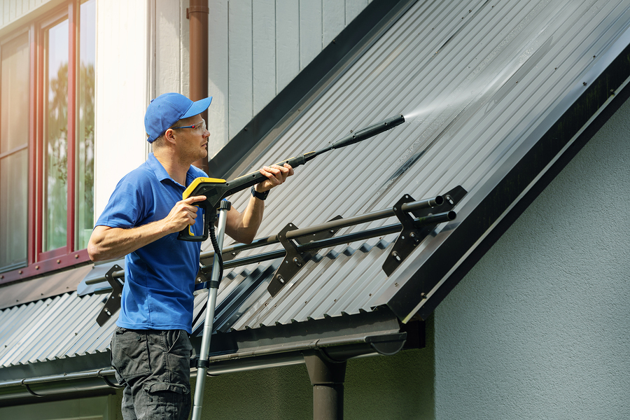 professional exterior cleaner cleaning roof and gutter